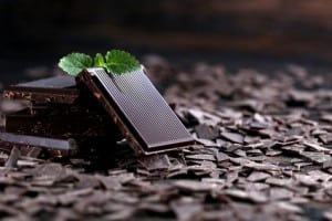Broken dark chocolate and chocolate flakes on a wooden table NutriShield Multi Vitamins and Minerals